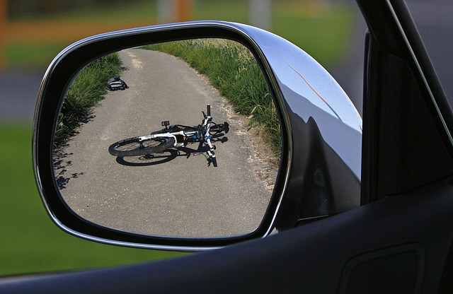 Bicycle on the ground shown in car mirror.