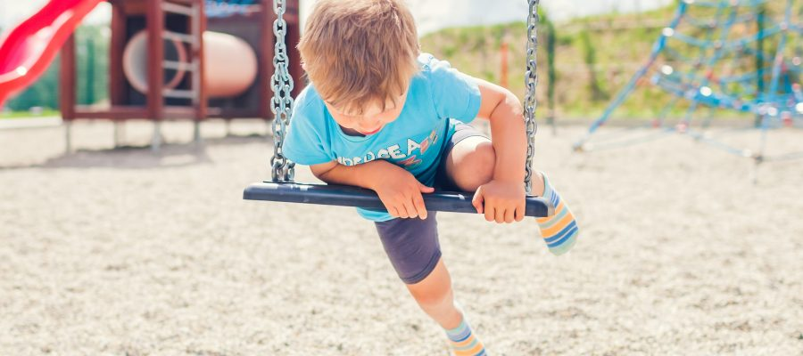Unsupervised child getting on a swing by himself