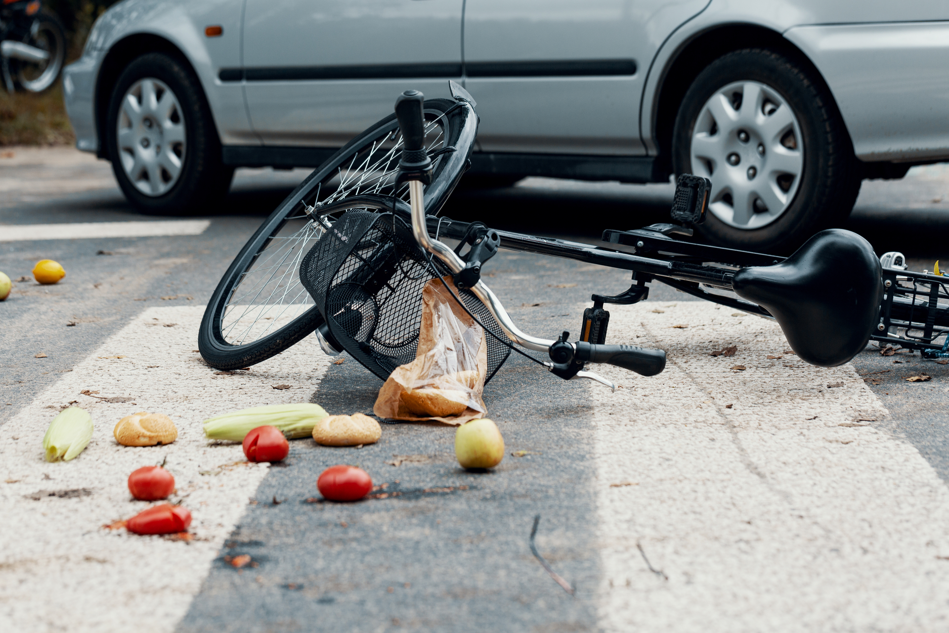 Groceries and broken bike on pedestrian crossing after collision with a car