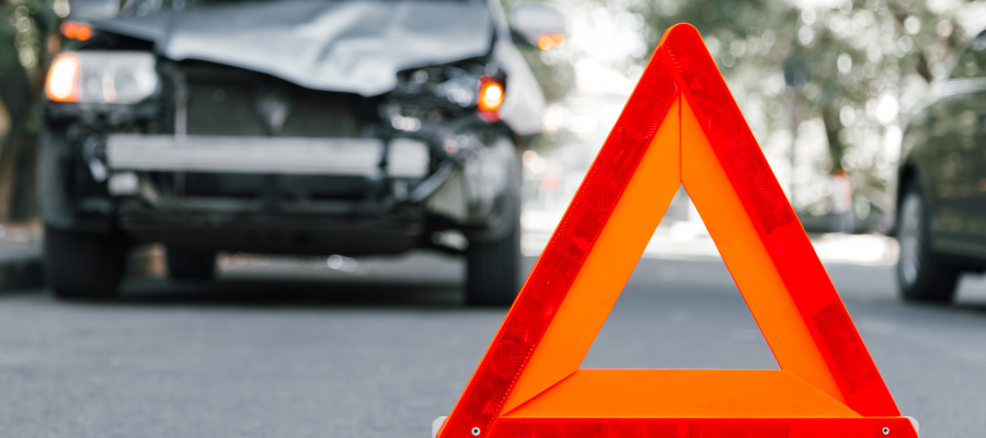 Red emergency stop triangle sign on road in car accident scene.